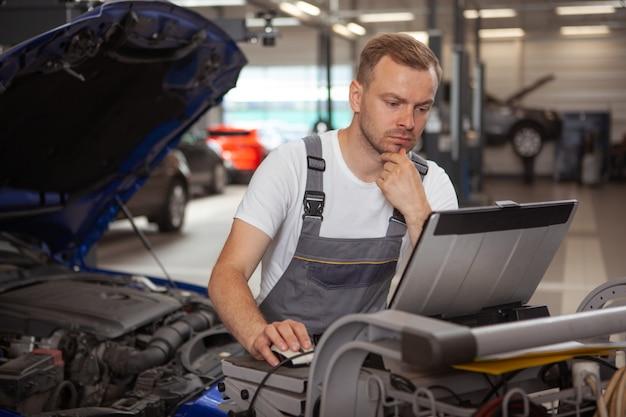 Meccanico maschio maturo che lavora al garage Foto Premium