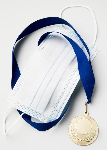 Medaglia sportiva accanto alla mascherina medica Foto Gratuite