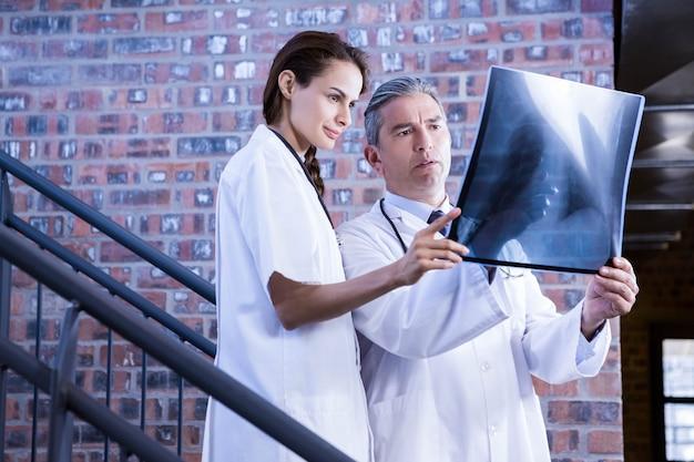 Medici che esaminano il rapporto dell'ascia sulla scala in ospedale Foto Premium