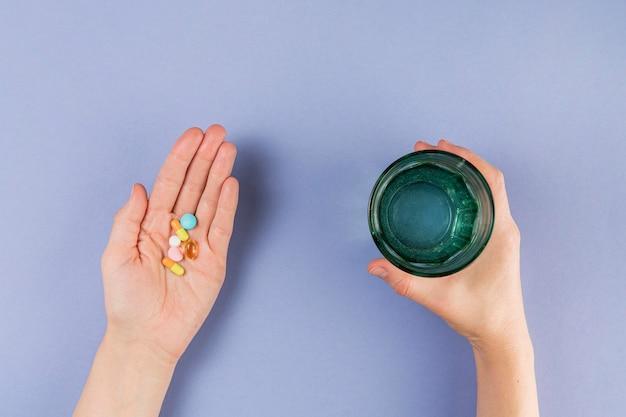 Medicina e vetro della tenuta della mano di vista superiore con acqua Foto Gratuite