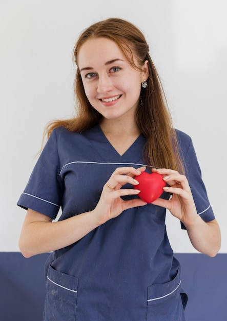 Medico a colpo medio che tiene giocattolo a forma di cuore Foto Gratuite