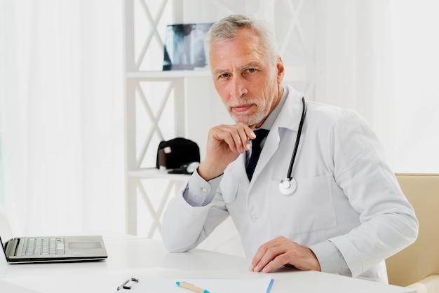 Medico alla sua scrivania con la mano sul mento Foto Gratuite