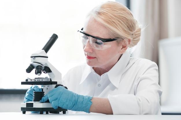 Medico analizzando con un microscopio Foto Gratuite