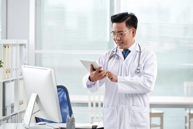 Medico asiatico che usando app medica sul suo dispositivo digitale Foto Gratuite