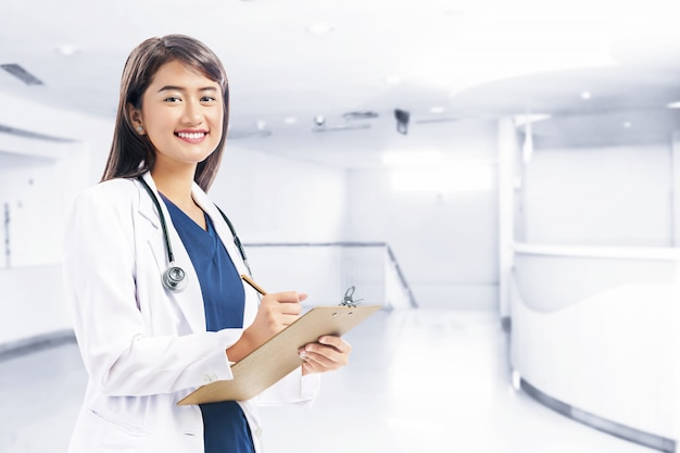 Medico asiatico della donna in appunti bianchi della tenuta del cappotto e dello stetoscopio del laboratorio Foto Premium