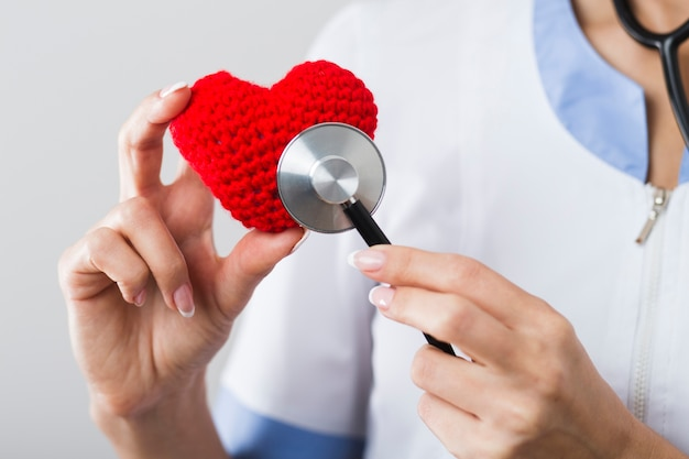 Medico che ascolta un cuore di peluche Foto Gratuite