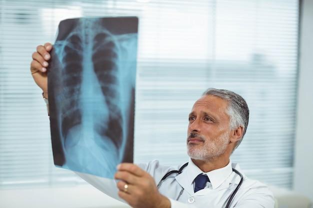 Medico che controlla un rapporto dei raggi x in clinica Foto Premium