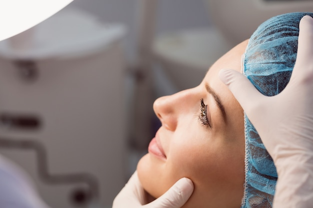 Medico che esamina la faccia della donna per il trattamento cosmetico Foto Gratuite