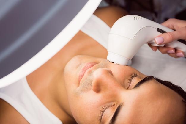 Medico che esegue la depilazione laser sul viso del paziente Foto Gratuite