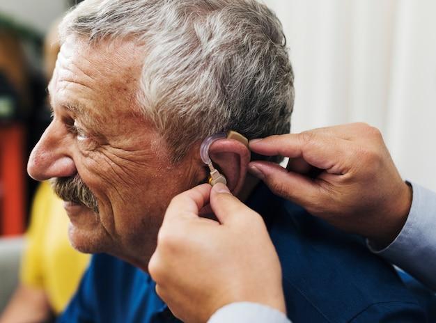 Medico che inserisce l'apparecchio acustico all'orecchio del paziente Foto Premium