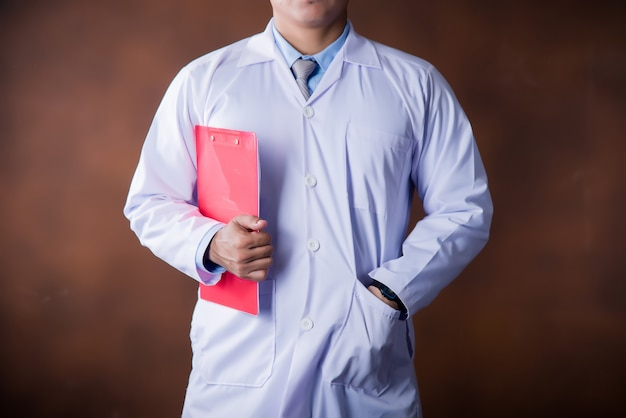 Medico che lavora in possesso di un blocco per appunti Foto Gratuite