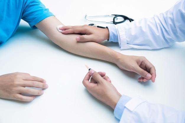 Medico che mette una vena del braccio bendaggio adesivo dopo analisi del sangue o iniezione di vaccino Foto Premium