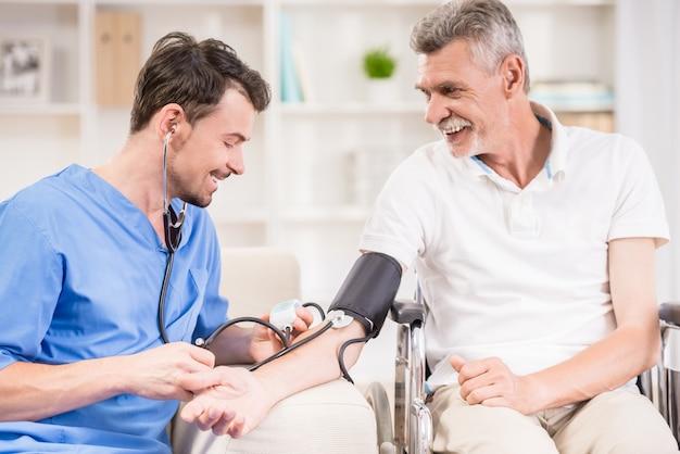 Medico che misura la pressione sanguigna al paziente più anziano. Foto Premium