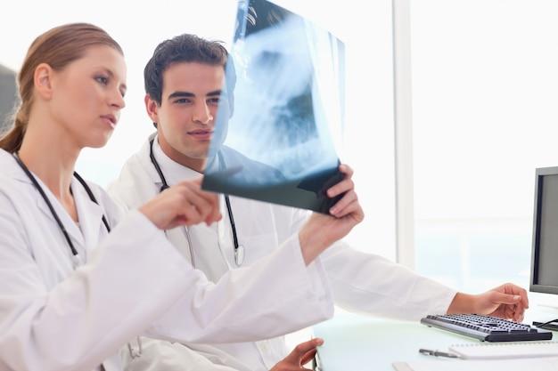 Medico che mostra al suo collega una radiografia Foto Premium