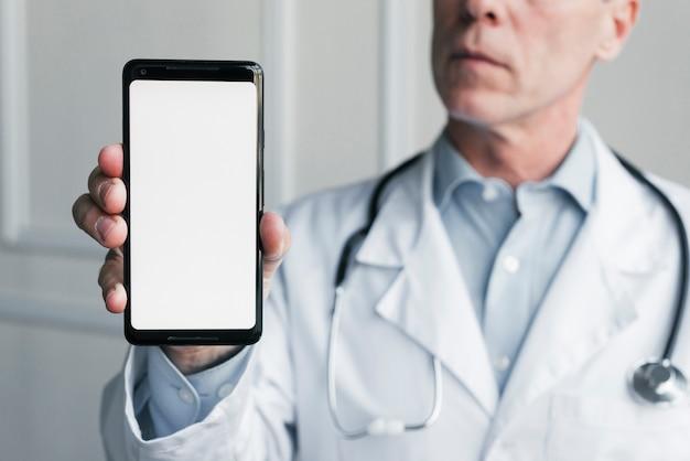Medico che mostra un telefono cellulare Foto Gratuite