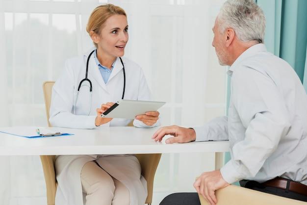 Medico che parla con paziente mentre si tiene compressa Foto Gratuite