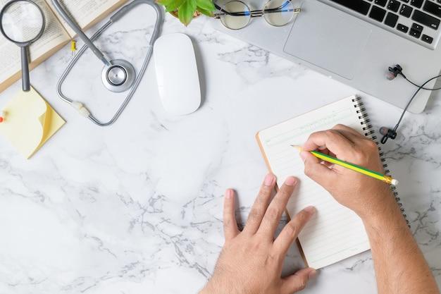 Medico che scrive taccuino in bianco sulla tabella di marmo Foto Premium