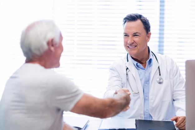 Medico che stringe la mano con l'uomo senior Foto Premium