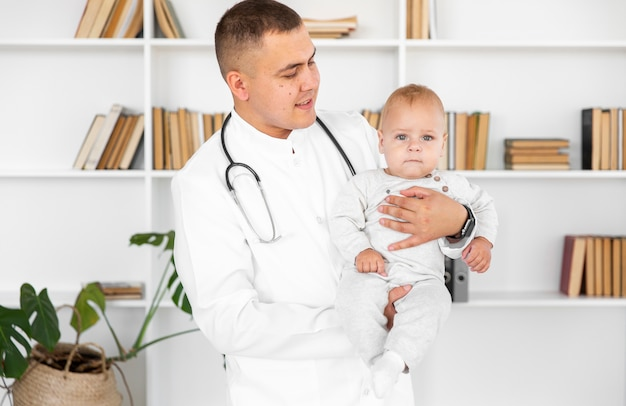 Medico che tiene piccolo bambino e guardandolo Foto Gratuite