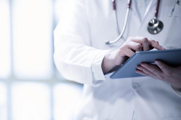 Medico che utilizza compressa astuta per lavoro nell'ospedale Foto Premium