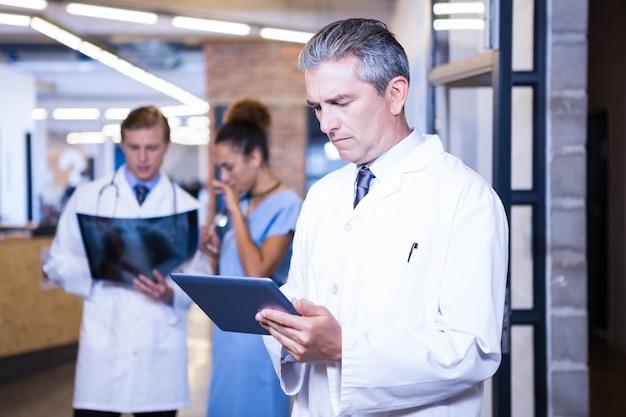 Medico che utilizza compressa digitale nell'ospedale e colleghi che stanno dietro e che discutono Foto Premium