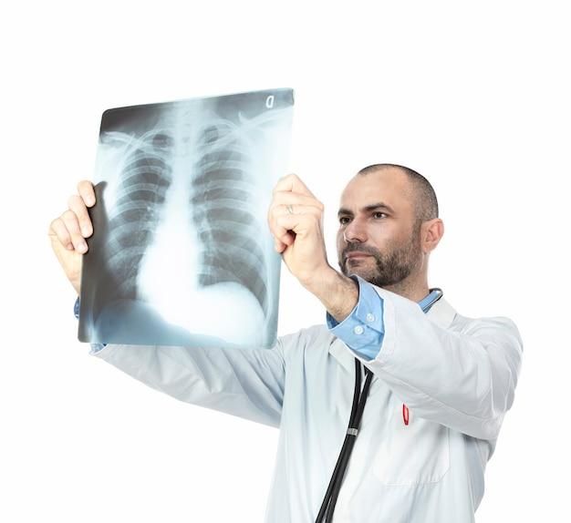Medico con barba e abito esamina una radiografia del torace Foto Premium