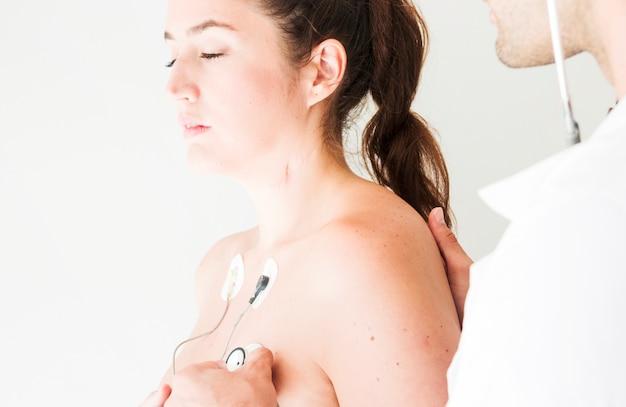 Medico con lo stetoscopio che controlla la respirazione della signora Foto Gratuite