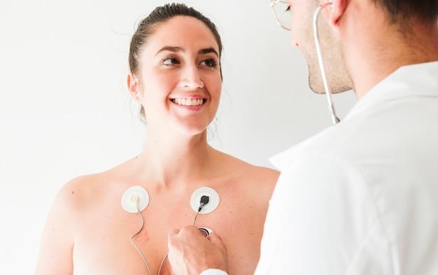 Medico con stetoscopio vicino donna con elettrodi Foto Gratuite