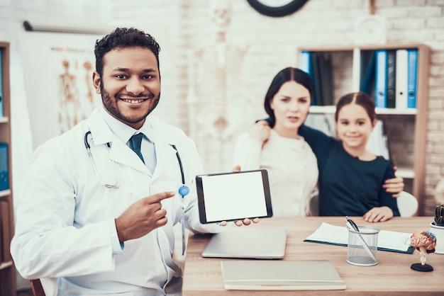 Medico con tablet guardando la fotocamera e sorridente. Foto Premium