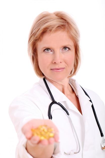 Medico della donna adulta con le pillole in lei consegna il fondo bianco Foto Gratuite