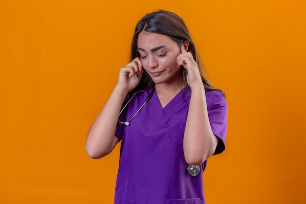 Medico della giovane donna in uniforme medica con fonendoscopio che sta con gli occhi chiusi che si sentono a file avendo forte mal di testa sopra fondo arancio isolato Foto Gratuite