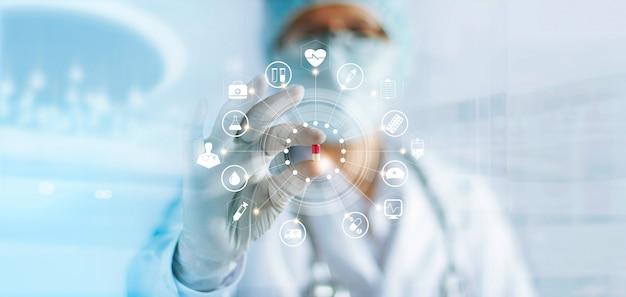 Medico della medicina che tiene una pillola della capsula di colore a disposizione con collegamento di rete medico dell'icona, concetto della rete di tecnologia medica Foto Premium
