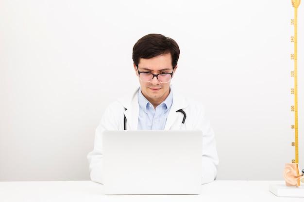 Medico di vista frontale che lavora su un computer portatile Foto Gratuite
