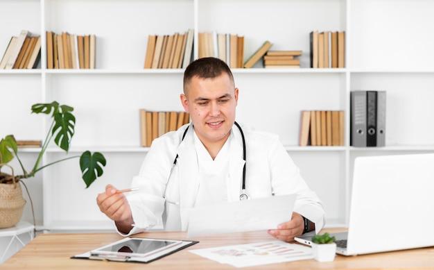Medico di vista frontale che osserva su una ricetta Foto Gratuite