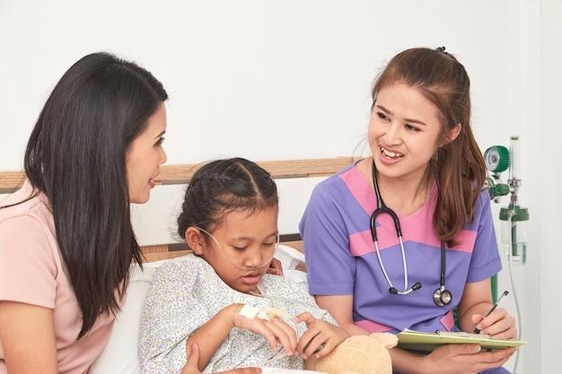 Medico e bambino con la madre in ospedale Foto Premium