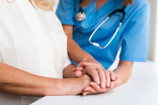 Medico e donna anziana che si tengono per mano primo piano Foto Gratuite