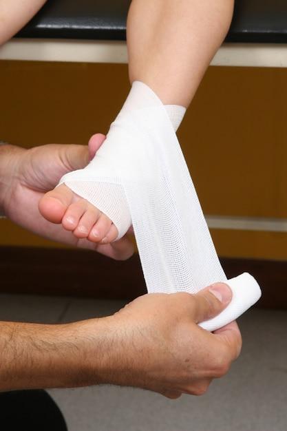 Medico eseguendo una benda alla caviglia su una ragazza Foto Premium