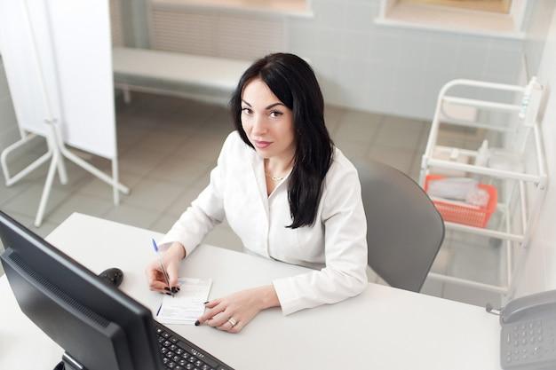 Medico femminile che lavora al computer portatile, scrivendo il blocco note di prescrizione con informazioni record sullo scrittorio in ospedale o clinica, sanità e concetto medico Foto Premium