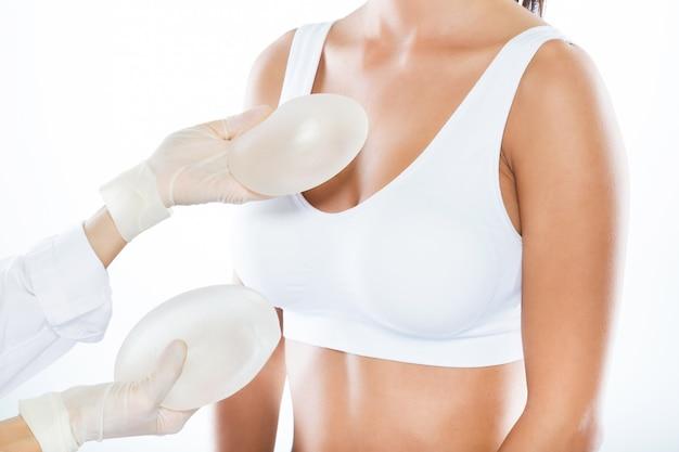 Medico femminile che sceglie la protesi mammaria con il suo paziente sopra fondo bianco. Foto Gratuite
