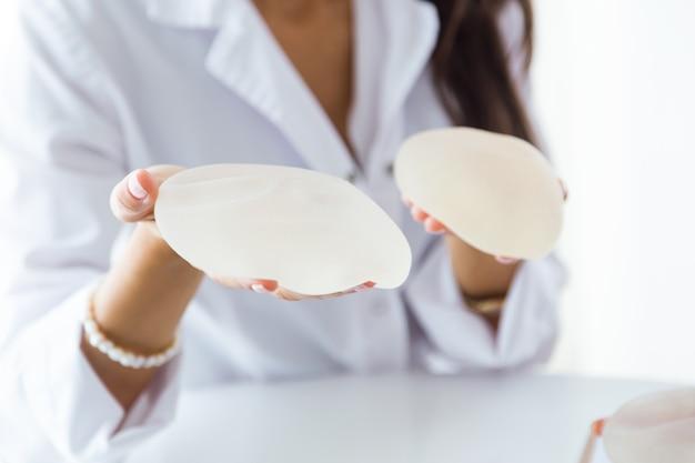 Medico femminile che sceglie la protesi mammaria nell'ufficio. Foto Gratuite