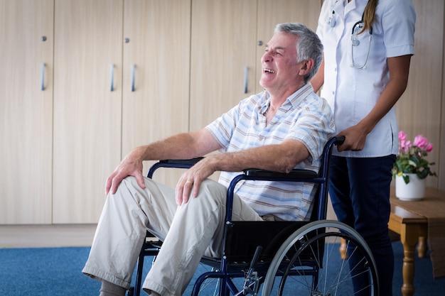 Medico femminile che trasporta uomo maggiore sulla sedia a rotelle Foto Premium