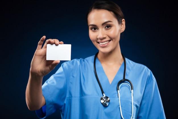 Medico grazioso che mostra la carta di identità o biglietto da visita e sorridere in bianco Foto Gratuite