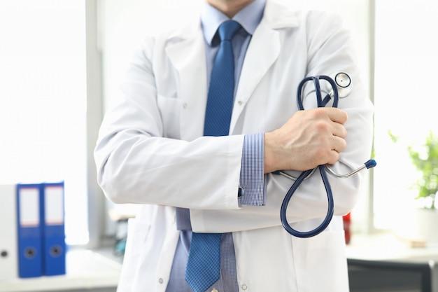 Medico in piedi in ufficio con lo stetoscopio in mano Foto Premium