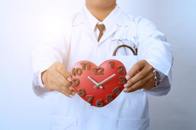 Medico in possesso di un orologio, concetto per i tempi, medici e sanitari Foto Premium