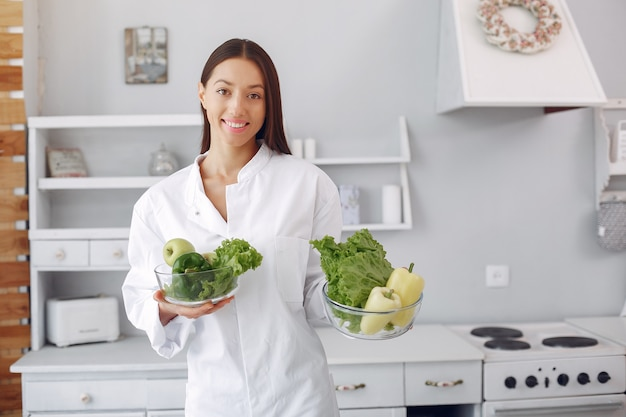 Medico in una cucina con verdure Foto Gratuite