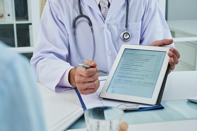 Medico irriconoscibile che estende la scheda digitale affinché il paziente anonimo compili il questionario Foto Gratuite