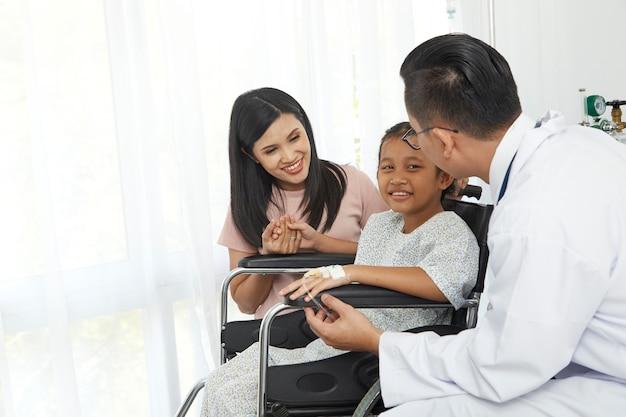 Medico maschio asiatico che parla con sedia a rotelle e madre del bambino piccolo, cura dell'ospedale di concetto Foto Premium