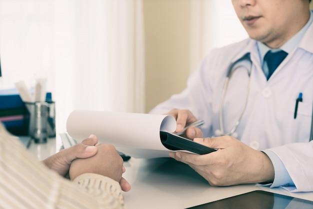 Medico maschio che spiega diagnosi al paziente. paziente della donna che sembra preoccupato quando ascolta le notizie del letto. Foto Premium