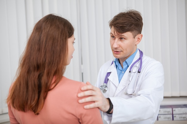Medico maschio maturo che lavora nella sua clinica, parlando con un paziente di sesso femminile. medico esperto che conforta il suo paziente sconvolto Foto Premium