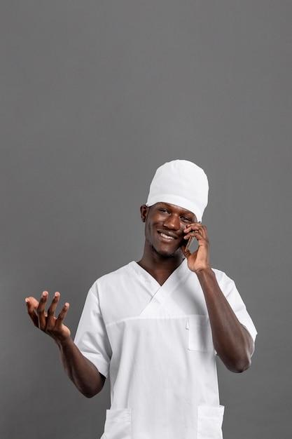 Medico maschio specialista sorride e parla al telefono Foto Gratuite